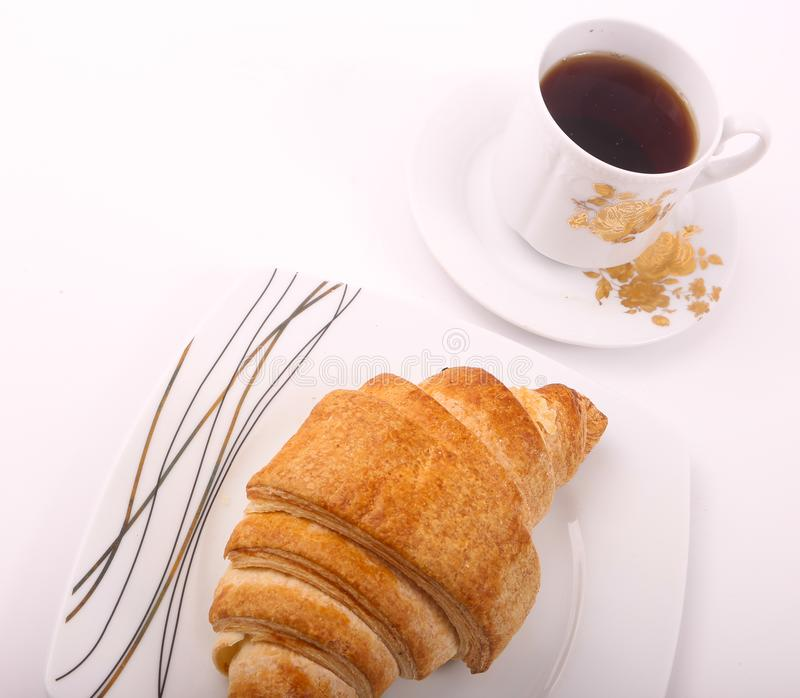 Croissant with tea. On white plate royalty free stock photo