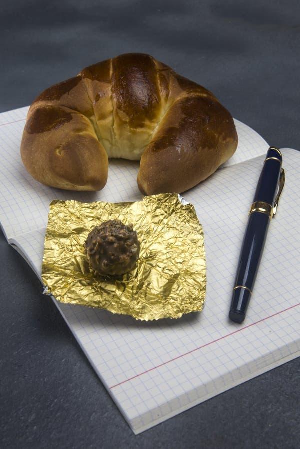 Croissant y bonbon en un cuaderno foto de archivo