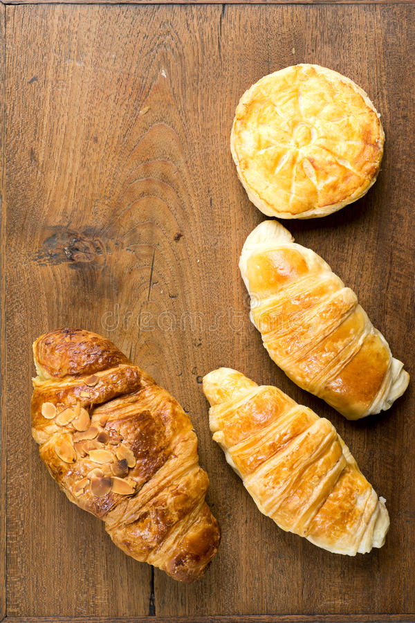 Croissantbakkerij en koekje op teakhout royalty-vrije stock afbeeldingen