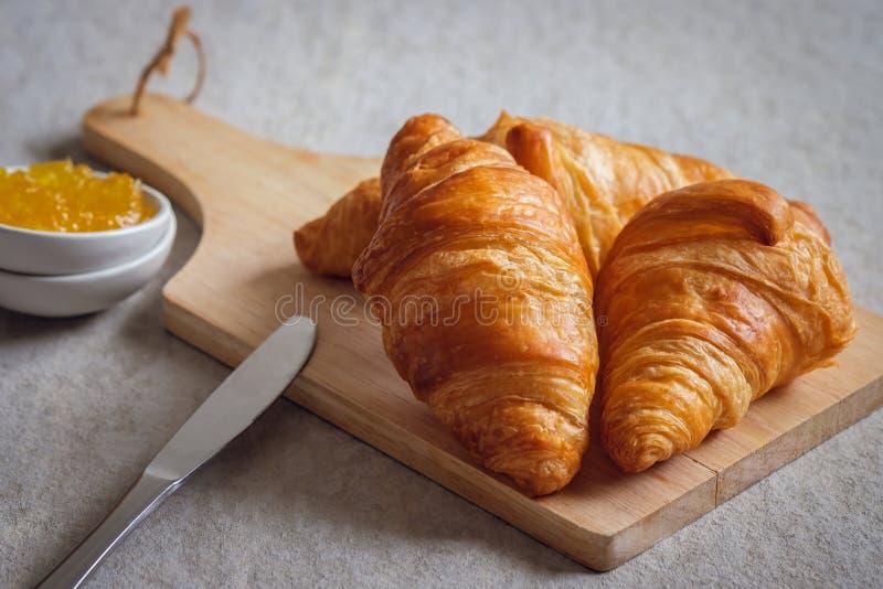 Croissanti freschi a bordo di legno e marmellata d'arancia in ciotola fotografia stock