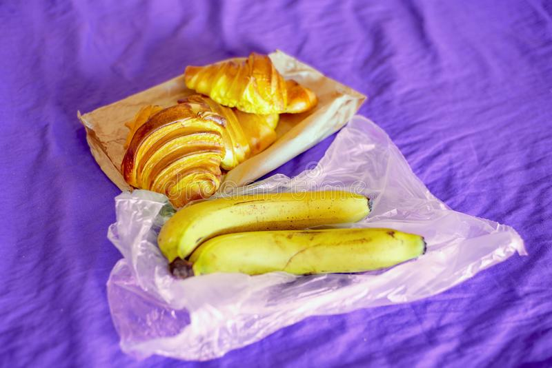 Croissants και μπανάνες που εξυπηρετούνται για το πρόγευμα στο ιώδες επιτραπέζιο ύφασμα του s στοκ φωτογραφίες με δικαίωμα ελεύθερης χρήσης