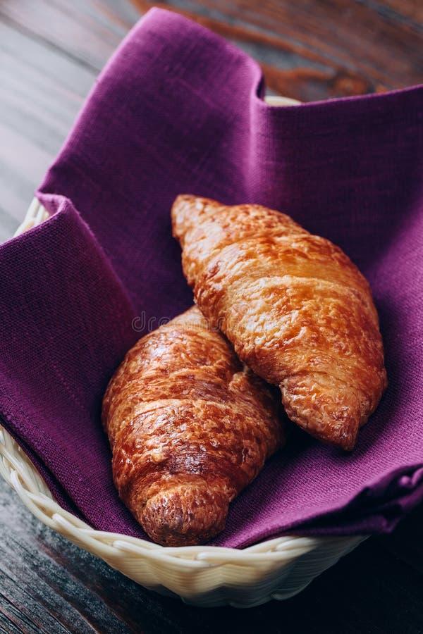 Croissants σε ένα καλάθι στον ξύλινο πίνακα στοκ εικόνα με δικαίωμα ελεύθερης χρήσης