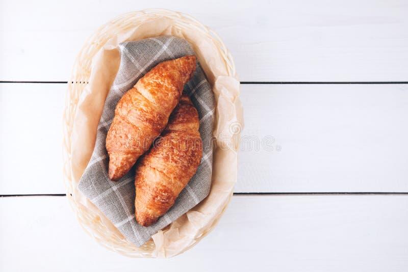 Croissants σε ένα καλάθι στον ξύλινο πίνακα στοκ εικόνες με δικαίωμα ελεύθερης χρήσης