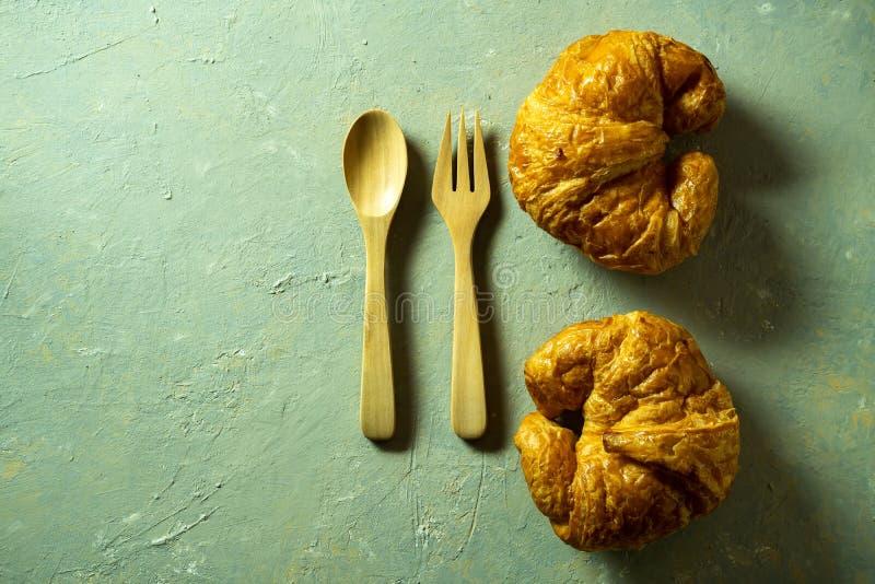 Croissants στο ξύλινο πιάτο με το κουτάλι και δίκρανο στον πίνακα στοκ εικόνα