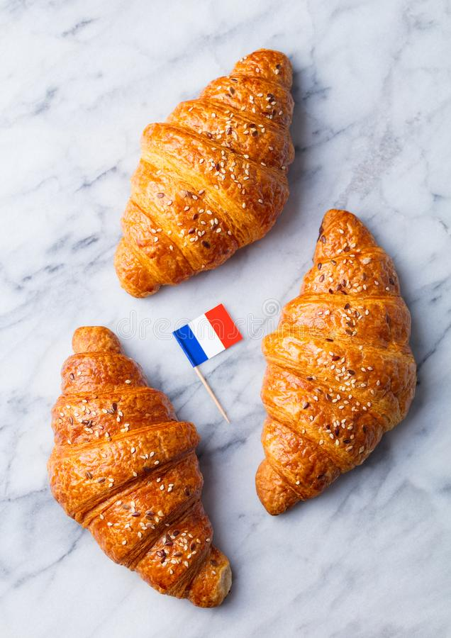 Croissants avec le drapeau français Fond de marbre photographie stock libre de droits