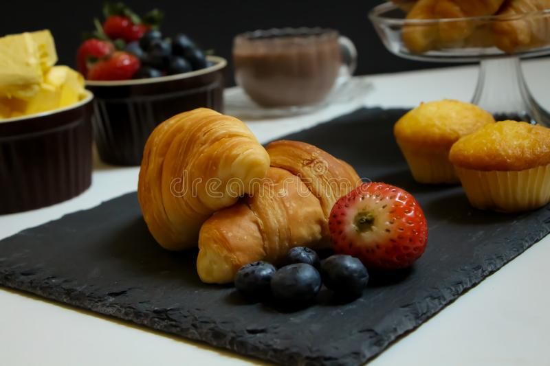 Croissants. Breakfast scence at home. Freshly baked croissants, muffins and fresh berries with a cup of hot chocolate stock image