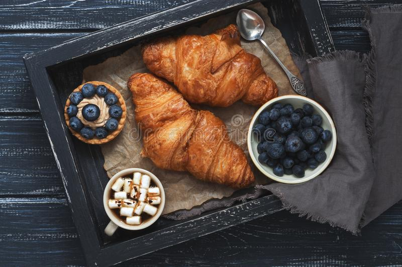 Croissants, cake with blueberries, coffee with marshmallows on a wooden tray with a napkin. Wooden dark background, top view. stock image