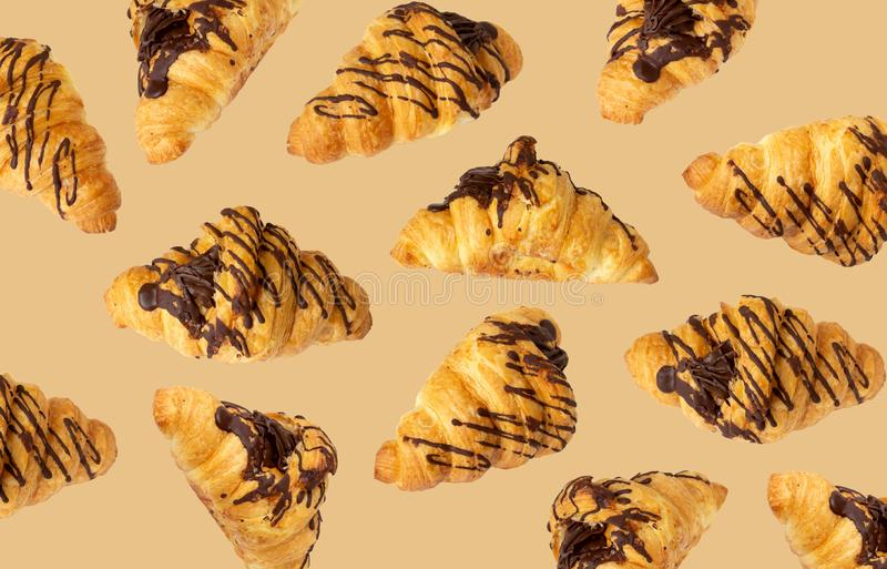 Croissants with chocolate cream flying over beige background. Delicious sweet food falling royalty free stock photo