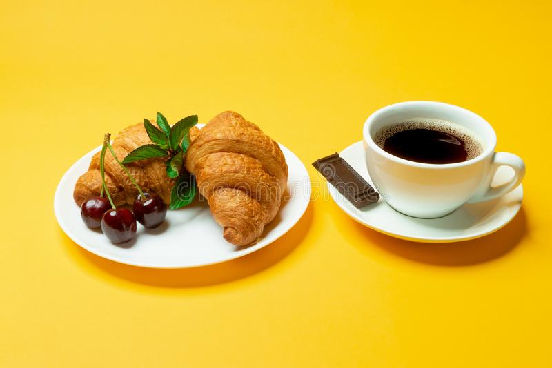 Croissants, coffe, chocolate and cherries on yellow background. Close up stock image