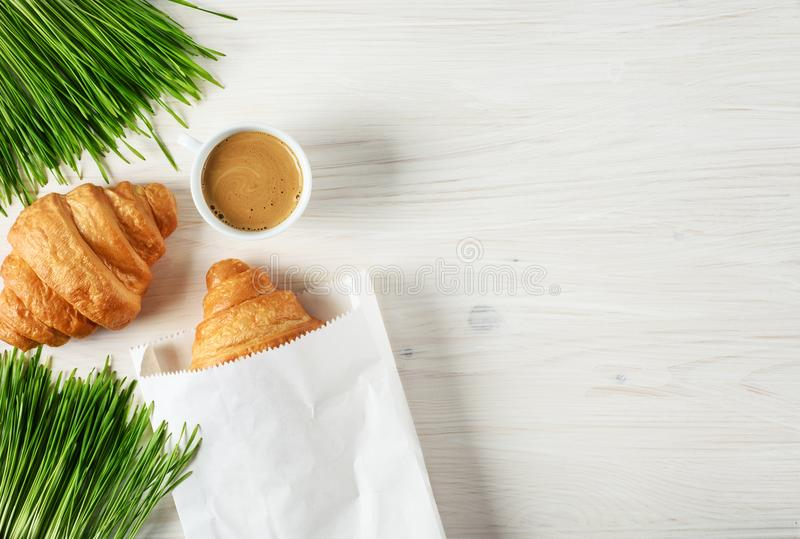 Croissants, coffee and sprouted wheat on a wooden background. Breakfast flat lay royalty free stock image