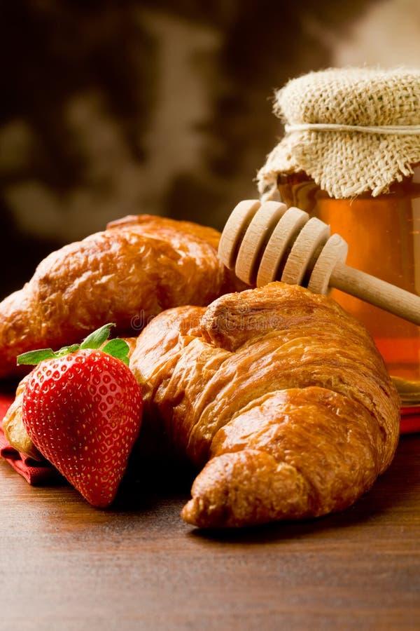 Croissants con miele e le fragole immagini stock libere da diritti