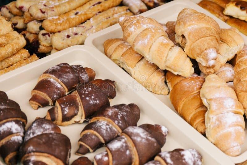 Croissants de chocolat et de crème dans la fenêtre de magasin photos libres de droits