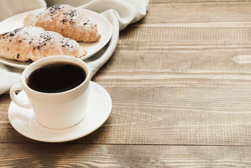 Croissants de chocolat et tasse fraîchement cuits au four de café noir sur la planche à découper en bois Fin vers le haut Copiez  images stock
