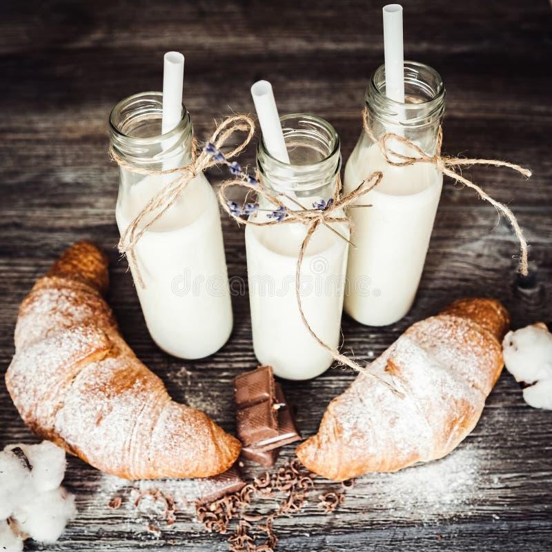 Croissants en flessen melk stock afbeelding