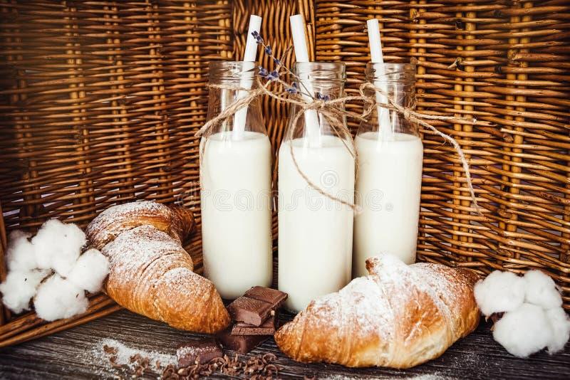 Croissants en flessen melk stock afbeeldingen