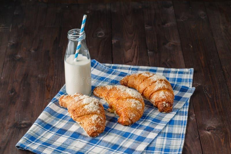 Croissants en flessen melk op houten achtergrond stock fotografie
