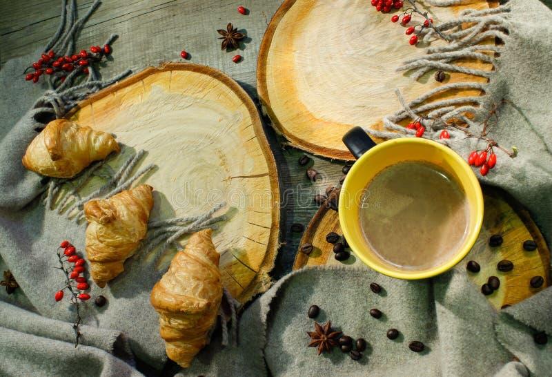 Croissants et une tasse de café sur une surface en bois parmi des baies couvrantes et rouges de laine Motif d'automne photos stock
