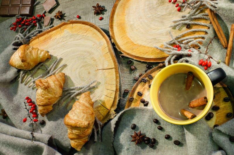 Croissants et une tasse de café sur une surface en bois parmi des baies couvrantes et rouges de laine Motif d'automne image stock