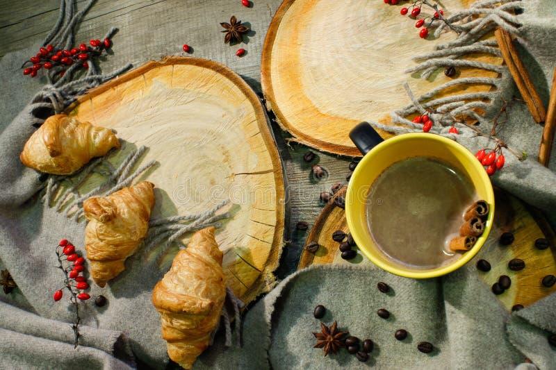 Croissants et une tasse de café sur une surface en bois parmi des baies couvrantes et rouges de laine Motif d'automne photo stock