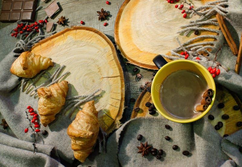 Croissants et une tasse de café sur une surface en bois parmi des baies couvrantes et rouges de laine Motif d'automne images libres de droits