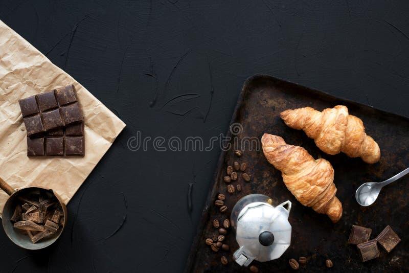 Croissants frais avec du chocolat, fabricant de café de geyser, grains de café sur le fond foncé de cru Déjeuner avec des croissa photo libre de droits