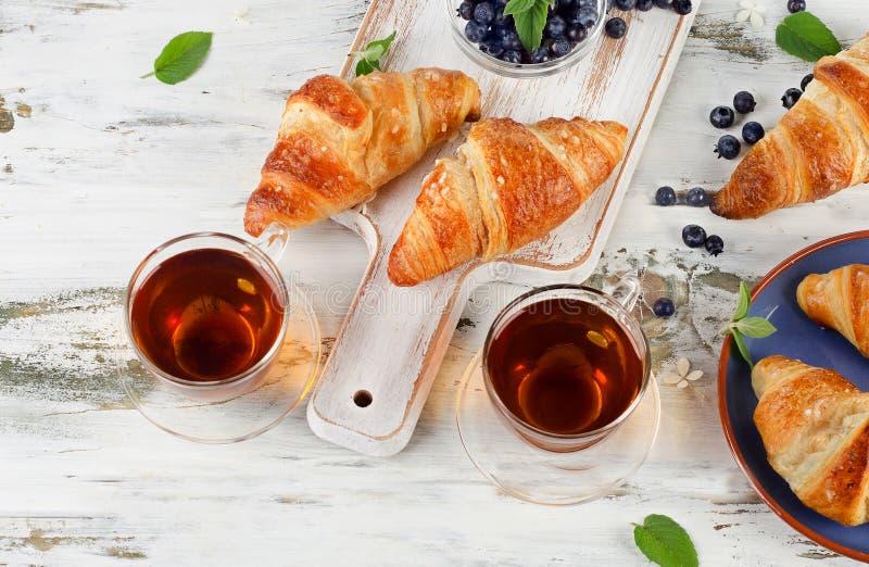Croissants frais avec les tasses en verre de thé noir photo libre de droits