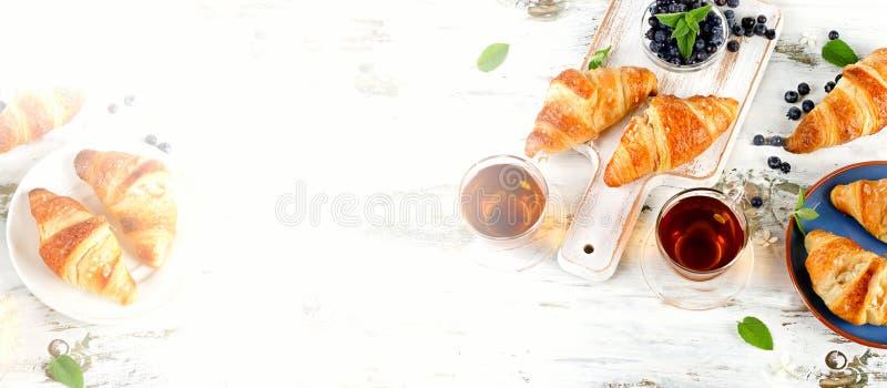 Croissants frais avec les tasses en verre de thé noir images stock
