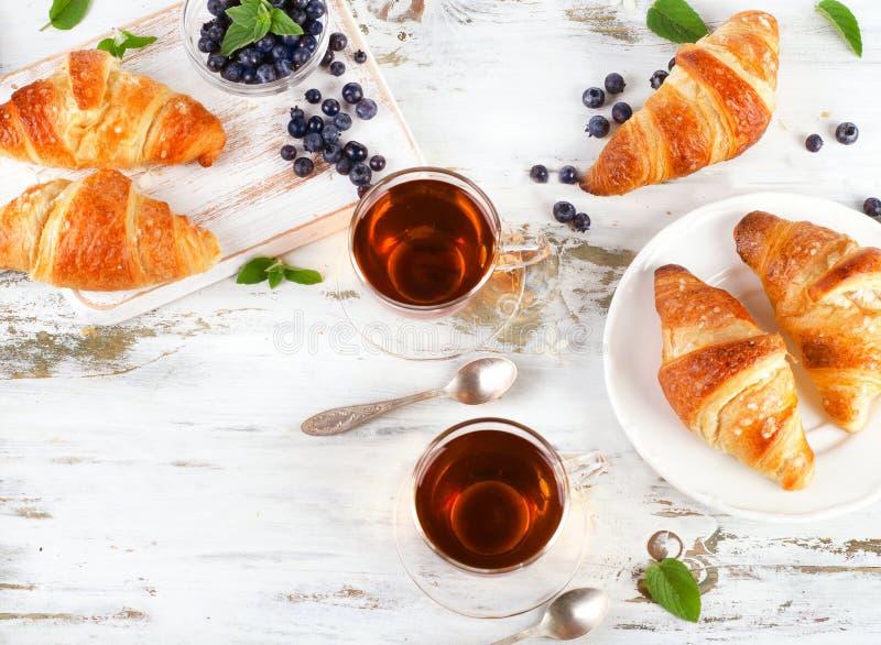 Croissants frais avec les tasses en verre de thé noir pour un petit déjeuner photos stock