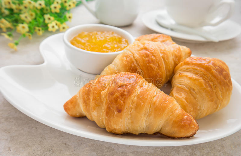 Croissants with jam on plate and coffee cup royalty free stock photography