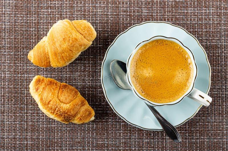 Croissants, kop met zwarte koffie, lepel op schotel op mat Hoogste mening royalty-vrije stock afbeelding