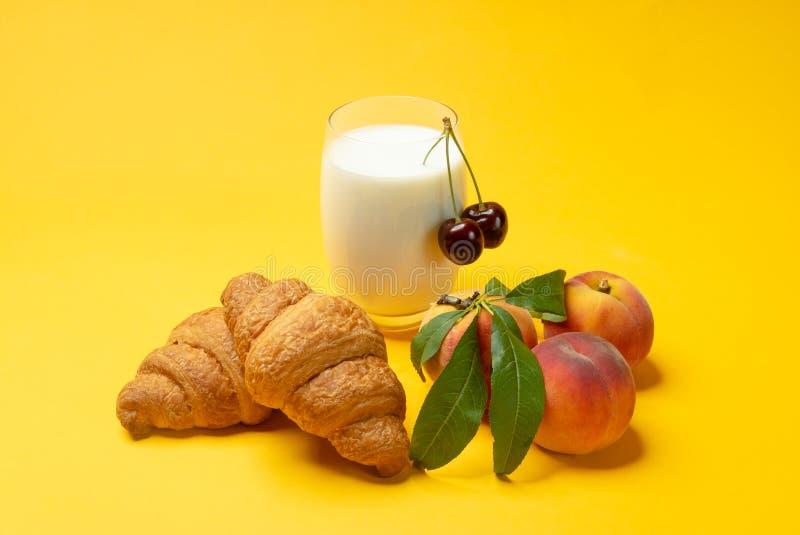 Croissants, melk, bloemen en perziken op gele achtergrond stock afbeeldingen