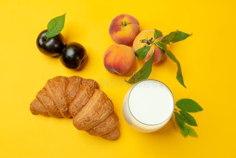 Croissants, melk, pruimen en perziken op gele achtergrond royalty-vrije stock foto
