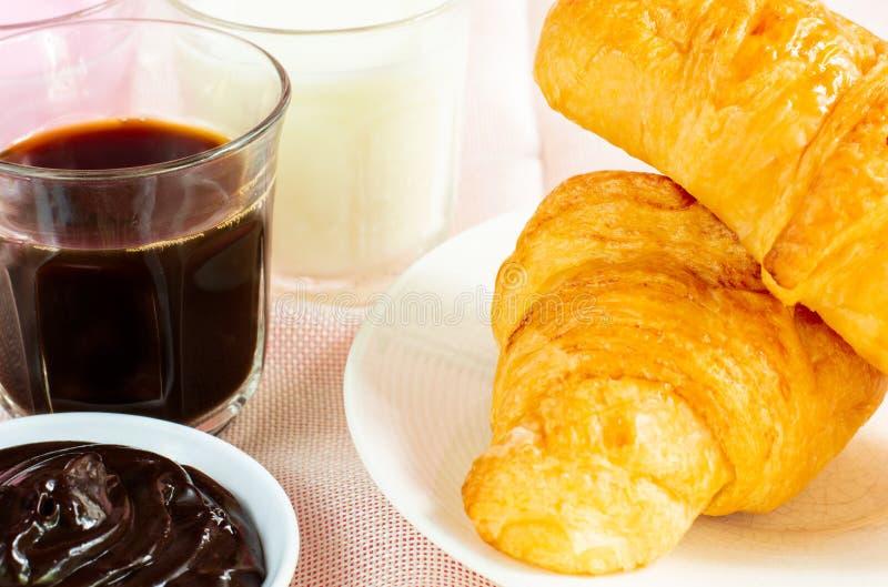 Croissants met glas Verse melk, koffie op roze achtergrond worden gediend die Het concept van het ontbijt royalty-vrije stock fotografie