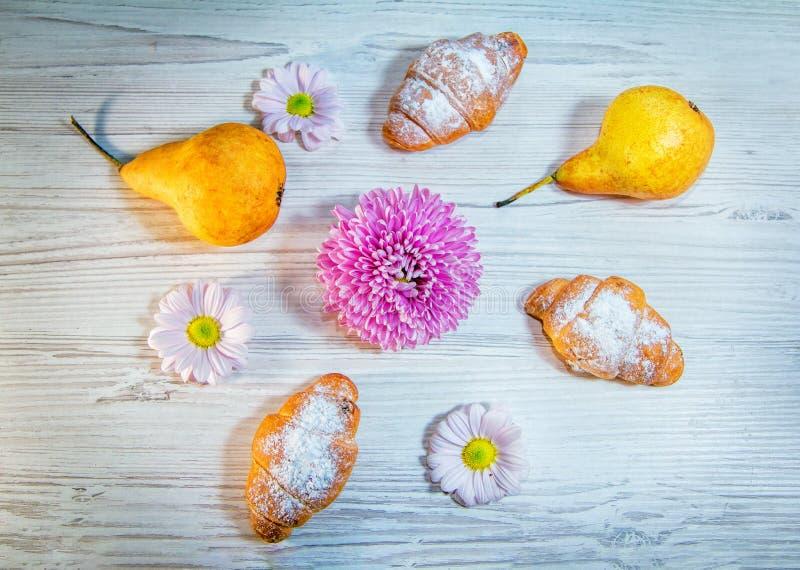Croissants met suikerpoeder en rijpe gele pruimen stock afbeelding