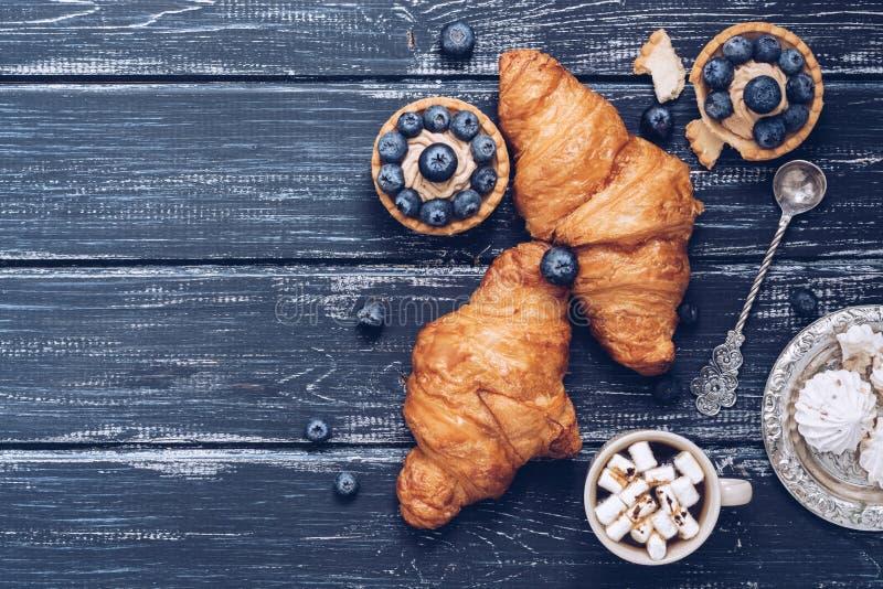 Croissants na błękitnym nieociosanym drewnianym tle, tort z czarnymi jagodami, bezy zdjęcia stock