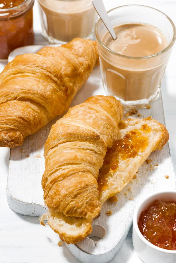 croissants with orange jam and coffee with milk, vertical royalty free stock photos
