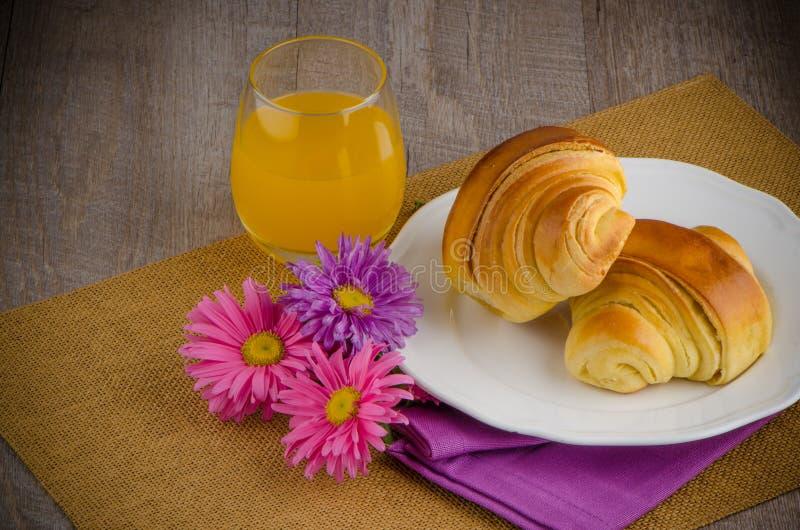 Croissants with orange juice stock photos