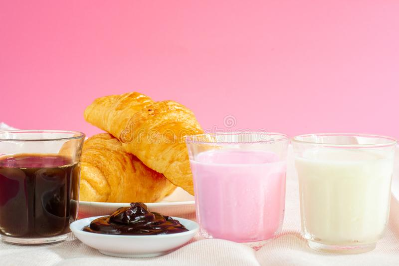 Croissants served with glass of Fresh milk, coffee on pink background. Breakfast concept. Croissants served with glass of Fresh milk, Black coffee on pink royalty free stock image