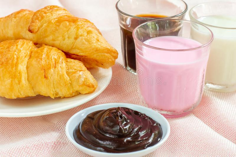 Croissants served with glass of Fresh milk, coffee on pink background. Breakfast concept. Croissants served with glass of Fresh milk, coffee on pink background royalty free stock photos