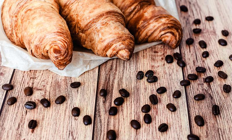 Croissants wrapped in baking paper and spilled coffee beans on wooden table. Top view. Close-up, background, beautiful, breakfast, crust, delicious, dessert royalty free stock image
