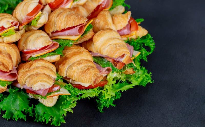 Croissants z baleronem, serem i pomidorem na talerzu, fotografia stock