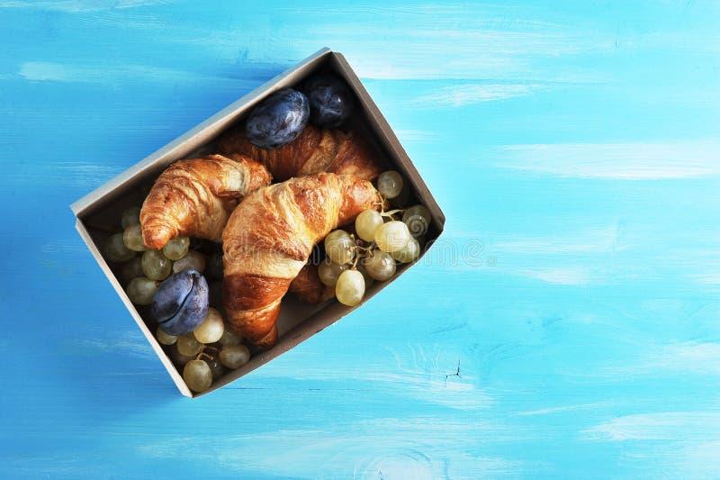 Croissants z owoc w pudełku na błękitnym drewnianym tle zdjęcie royalty free