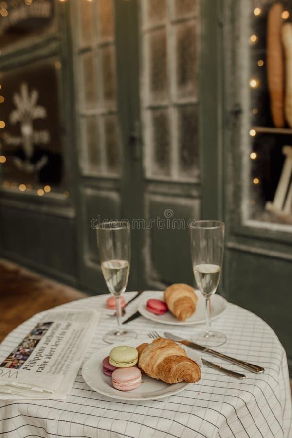 Croissantsand caseiro, campo e bolinhos de amêndoa Há café à moda do café da manhã de papel e francês com luz no imagem de stock