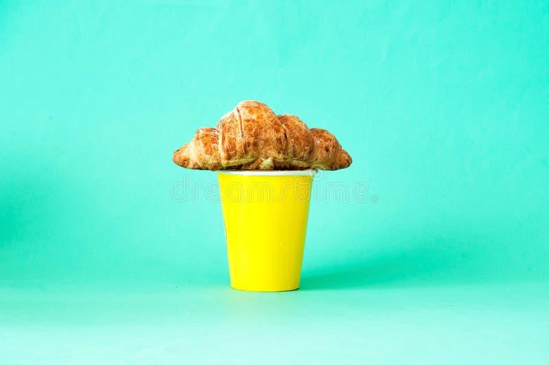 Croissantsandwiches en koffie in gele beschikbare kop stock foto