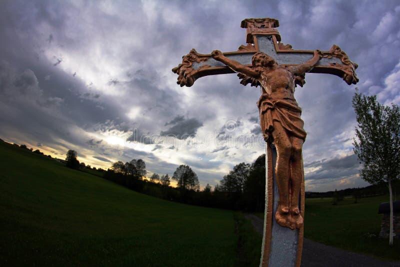 Croix chrétienne contre le ciel orageux image libre de droits