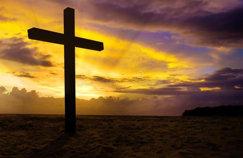 Croix chrétienne sur le coucher du soleil image libre de droits