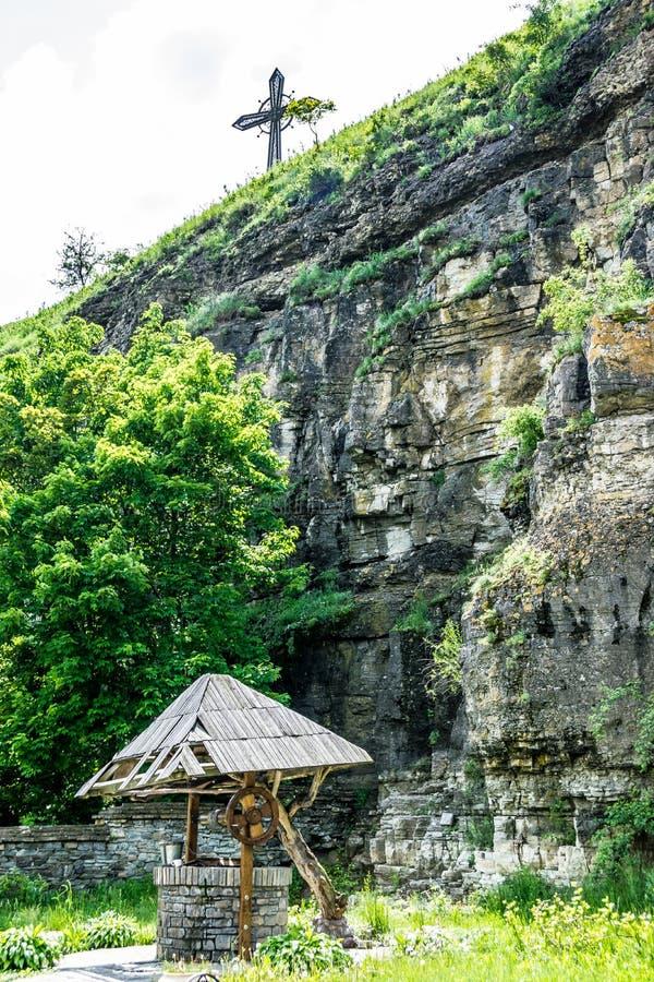 Croix chrétienne sur une roche et un vieux puits photo stock