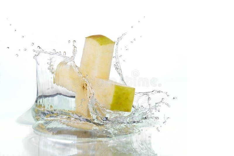 Croix d'Apple éclaboussant dans l'eau photographie stock libre de droits