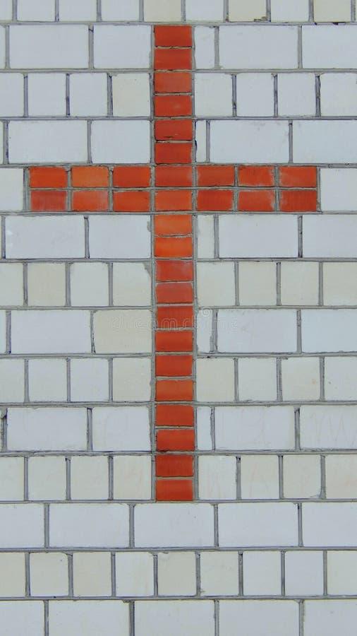 Croix de brique rouge sur un mur de la brique blanche photo libre de droits