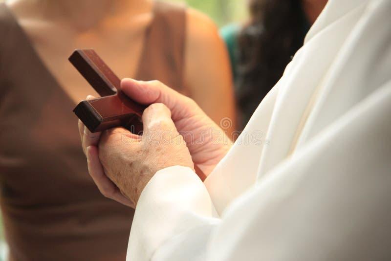 Croix de fixation de prêtre dans des mains photo libre de droits